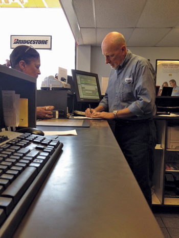 Paul Davidson at the counter of his East Falmouth, MA, shop with a customer.